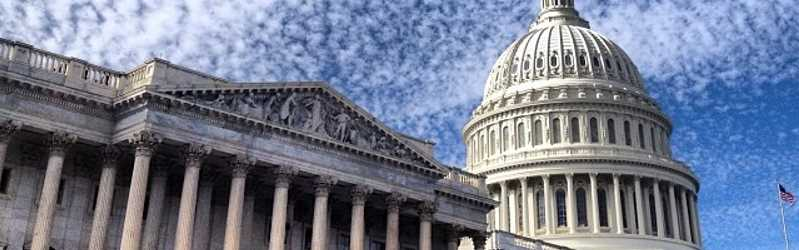 Image of the United States Capitol with sky and clouds in the background.