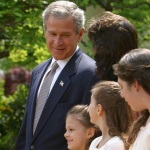 President George W. Bush looks toward Lacy Lyons, center, before signing the PROTECT Act of 2003, in the Rose Garden Wednesday, April 30, 2003. Lacy and her sister were found after an AMBER alert in Florida. Source: The White House Archives