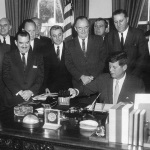 President John F. Kennedy signs the Peace Corps bill in the Oval Office of the White House