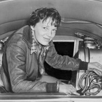 Photo of Amelia Earhart seated in airplane, checking equipment